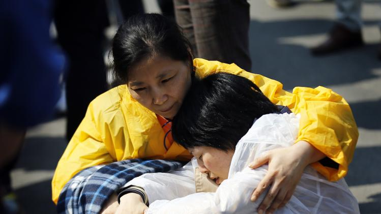 "Family member of a passenger missing after the South Korean ferry ""Sewol"" capsized is given a hug during a protest in Jindo"