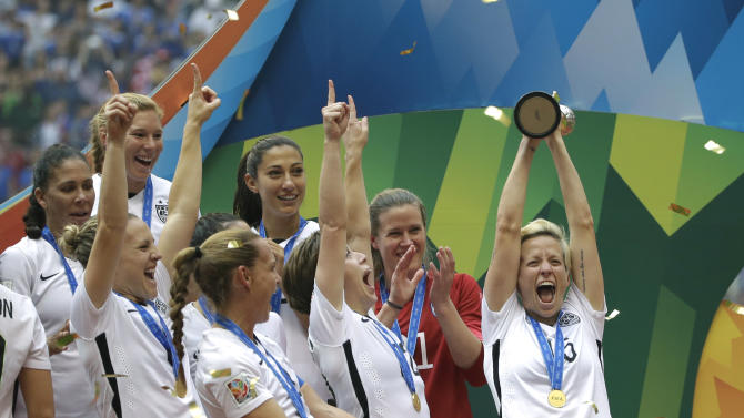 United States' Megan Rapinoe, right, holds up the trophy as she celebrates with teammates after the U.S. beat Japan 5-2 in the FIFA Women's World Cup soccer championship in Vancouver, British Columbia, Canada, Sunday, July 5, 2015. (AP Photo/Elaine Thompson)