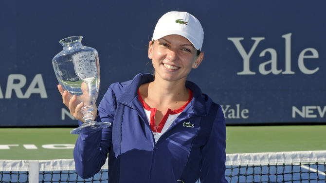 Simona Halep, of Romania, holds the trophy after her 6-2, 6-2, victory over Petra Kvitova, of the Czech Republic, in the final of the New Haven Open tennis tournament in New Haven, Conn., on Saturday, Aug. 24, 2013. (AP Photo/Fred Beckham)