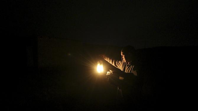 Ravshan, a Crimean Tatar, uses a burning oil lamp due to a power cut inside his house in the village of Strogonovka