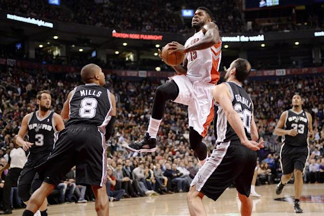 Toronto Raptors forward Amir Johnson (15) drives to the net between San Antonio Spurs guard Manu Ginobli (20) and guard Patty Mills (8) as guard Marco Belinelli (3) and forward Boris Diaw (33) stand b