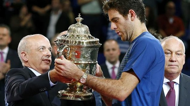 Swiss President Ueli Maurer (L) hands over the winner's trophy to Juan Martin Del Potro of Argentina (C) after winning his final match against Switzerland's Roger Federer at the Swiss Indoors (Reuters)