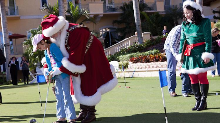 "Amber Shiver, 10, left, is taught how to use a putter by Santa Claus during the Macy's National Santa Tour at the The Ritz Carlton Golf Resort in Naples, Fla., Friday, Dec. 21, 2012. Santa made the stop at the resort to see ten Make-A-Wish children and their families as part of the Macy's national tour. Now in its fifth year, Macy's ""Believe campaign invites children to mail letter to Santa using Macy's Santa Mail letterboxes. Macy's donates a dollar for each letter mailed in store up to $1 million, to Make_A-Wish. (Erik Kellar/AP Images for Macy's)"