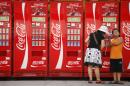 In this Aug. 9, 2008 file photo, a woman and boy stand near Coca-Cola vending machines on the Olympic Green at the 2008 Beijing Olympics in Beijing. When beverage giants Coca-Cola and PepsiCo turned in their quarterly results last week, both blamed the dollar for cutting into their profits because, like most U.S. corporations, they rely on overseas sales. (AP Photo/Peter Morgan, file)
