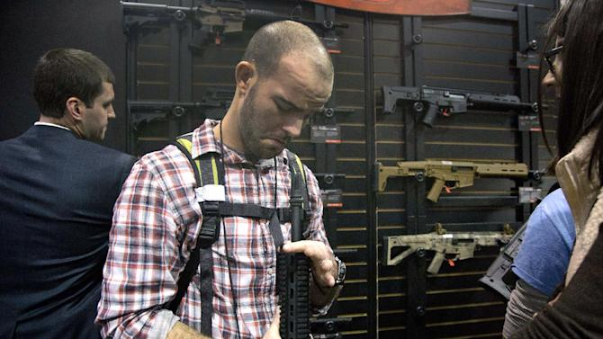 Will Michaels of Homer, La., examines a Bushmaster M4 A3 Carbine 300 AAC Blackout rifle at the Bushmaster exhibit during the Shooting Hunting Outdoor Tradeshow, Tuesday, Jan. 15, 2013, in Las Vegas. Michaels, who owns a sporting goods store, said while his gun sales focus primarily on bolt action hunting rifles, he and his clients have taken an interest in assault rifles over the last five years because of an expanding wild hog problem in his region. The National Shooting Sports Foundation was focusing its 35th annual SHOT Show on products and services new to what it calls a $4.1 billion industry, with a nod to a raging national debate over assault weapons. (AP Photo/Julie Jacobson)
