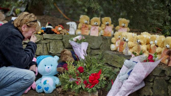 Cheryl Girardi, of Middletown, Conn., kneels beside 26 teddy bears, each representing a victim of the Sandy Hook Elementary School shooting, at a sidewalk memorial, Sunday, Dec. 16, 2012, in Newtown, Conn. A gunman walked into Sandy Hook Elementary School in Newtown Friday and opened fire, killing 26 people, including 20 children.(AP Photo/David Goldman)