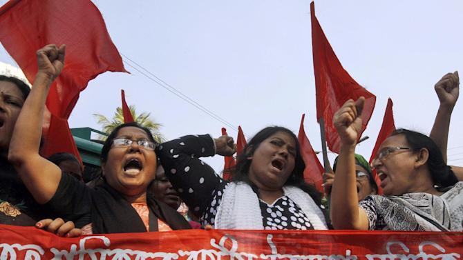"FILE - In this Nov. 30, 2012 file photo, Bangladeshi garment workers shout slogans as they participate in a protest to mourn the death of the victims of a fire in a garment factory in Dhaka, Bangladesh. About a year before the fire, executives from Wal-Mart, Gap and other big clothing companies met nearby in the country's capital to discuss a legally binding contract that would govern safety inspections. But after a spokeswoman for Wal-Mart, the world's largest retailer, got up and said the proposal wasn't ""financially feasible,"" the effort quickly lost momentum. (AP Photo/Pavel Rahman, File)"