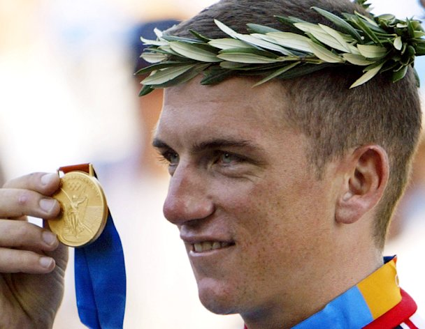 FILE - In this Aug. 18, 2004, file photo, Tyler Hamilton holds up his gold medal after the men's road individual time trial of the 2004 Olympic Games in the outskirts of Athens. The IOC is set to formally strip American cyclist Tyler Hamilton of his gold from the 2004 Athens Games and reassign the medals after his admission of doping, according to an Olympic official familiar with the case. (AP Photo/Eric Risberg, File)