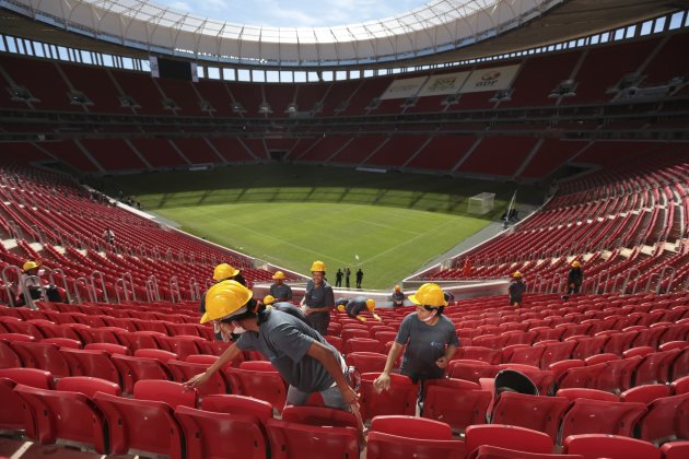 Workers inspect the seats of the National Mane Garrincha Stadium before its inauguration in Brasilia