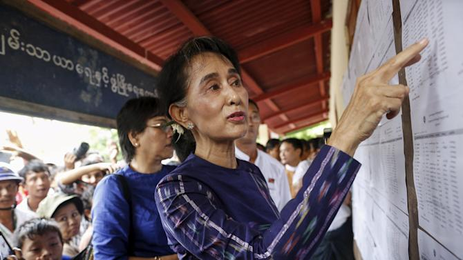 Suu Kyi checks a voters list at Warheinkha village in her constituency town Khawhmu