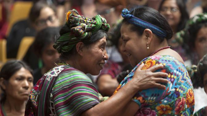 Nobel Peace Prize Laureate winner Rigoberta Menchu, right, hugs the relative of a victim of the country's civil before the verdict is announced in the genocide trial for Guatemala's former dictator Jose Efrain Rios Montt in Guatemala City, Friday, May 10, 2013. The Guatemalan court convicted Rios Montt on charges of genocide and crimes against humanity, sentencing him to 80 years in prison. The 86-year-old former general is the first former Latin American leader ever found guilty of such a charge. The war between the government and leftist rebels cost more than 200,000 lives and ended in peace accords in 1996. (AP Photo/Moises Castillo)