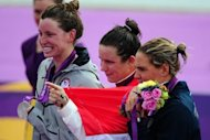 Hungary's Eva Risztov (centre) poses with her gold medal flanked by silver medallist Haley Anderson of the United States (left) and bronze medallist Italy's Martina Grimaldi (right) after winning the women's 10km open water swimming marathon at the London Olympics