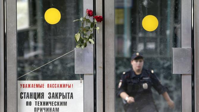Flowers in memory of victims of Tuesday's accident are left next to a sign informing passengers that the station is closed due to technical reasons, at the entrance to a metro station in Moscow
