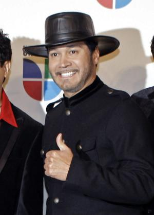 """FILE - This Nov. 13, 2008 file photo shows Oscar De La Rosa, lead singer for the Tejano group La Mafia, at the 9th annual Latin Grammy Awards in Houston. De La Rosa was knocked unconscious by a man in an unprovoked attack outside a Houston club on Monday, May 13, 2013. De La Rosa has facial cuts, eye damage and he lost two teeth.   La Mafia is considering whether to cancel any performances. The band, which formed in 1980 in Houston, won a Grammy in 2006 for the album, """"Nuevamente."""" (AP Photo/LM Otero, file)"""