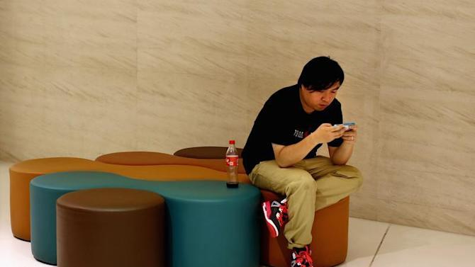 A man looks at his smart phone inside a shopping mall in downtown Shanghai