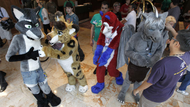 In this photo made on Thursday, June 14, 2012, people attending Anthrocon, some in animal costumes,  greet and mingle in the lobby of the Westin Convention Center hotel in Pittsburgh. Anthrocon, the world's largest convention for people who dress and assume the rolls of fictional animal characters, is back in its adopted home with an expected 5,000 participants between June 14 thru 17, 2012. (AP Photo/Keith Srakocic)