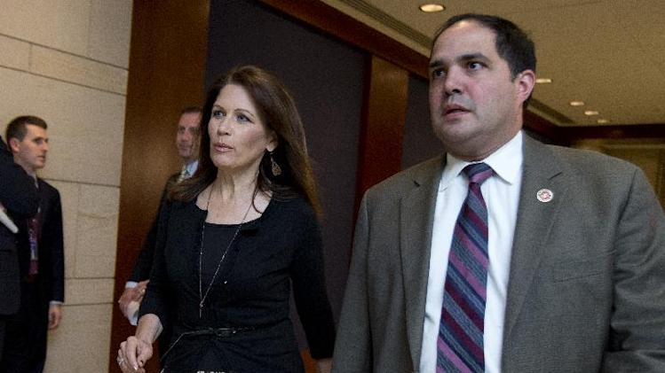 Rep. Michele Bachmann, R-Minn., arrives with staff member Javier Sanchez, right, for a closed all-member briefing on the NSA on Capitol Hill in Washington, Tuesday, June 11, 2013.    (AP Photo/Manuel Balce Ceneta)