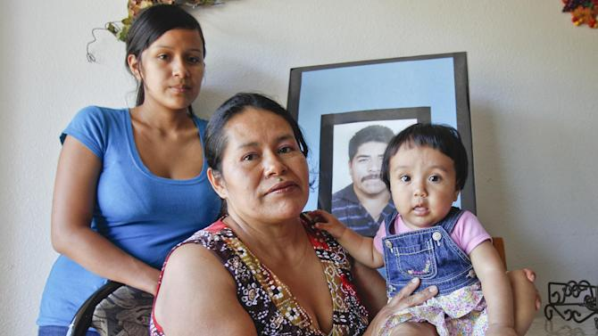 In this June 25, 2012 photo, Juana Garcia Martinez, with her daughter, Gladys Dominguez, 19, left, and granddaughter, Jazleen Dominguez, 8-months-old, pose in front of a photo of Juana Garcia's late husband, Ildefonso Martinez, in Vista, Calif.  Ildefonso Martinez died from dehydration trying to cross back into the United States after being deported last year. The death of migrants crossing the Southwest border has long been a tragic consequence of illegal immigration and, many say, the massive increase in U.S. border enforcement. For some, the tragedies are a powerful motivator in pushing Congress to act this year on a larger immigration reform package. (AP Photo/Lenny Ignelzi)