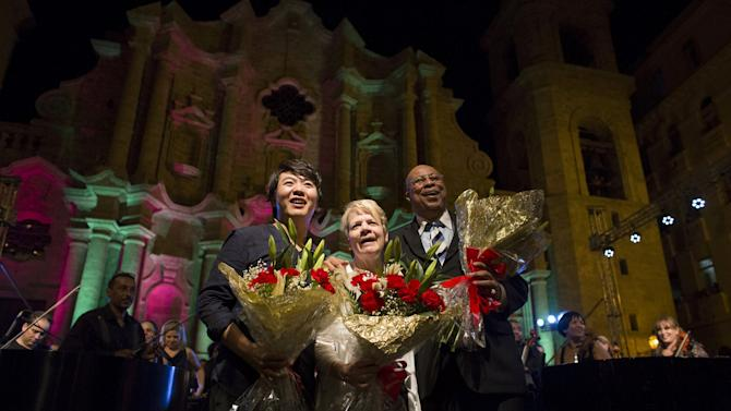 Cuban pianist and Grammy winner Chucho Valdes, pianist Lang Lang from China, and American conductor and violinist Marin Alsop, pose for photos after a concert at the Cathedral Square in Havana