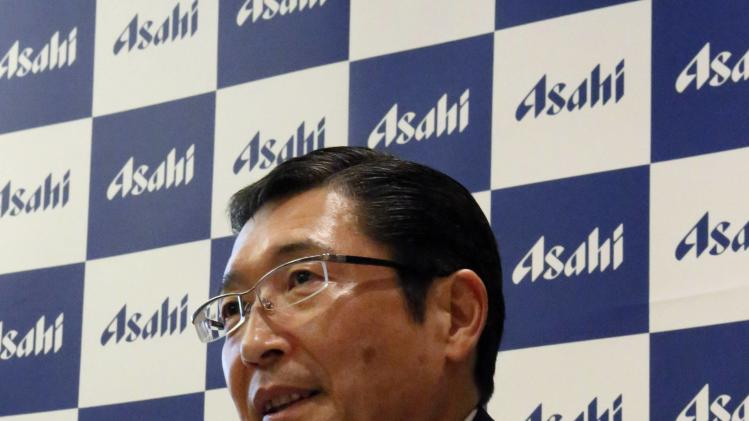 Koji, president of Asahi Breweries Ltd., speaks as cans of the new beer product Asahi Super Dry Premium and reissued beers Asahi Super Dry and Asahi Super Dry Black are seen next to him in Tokyo