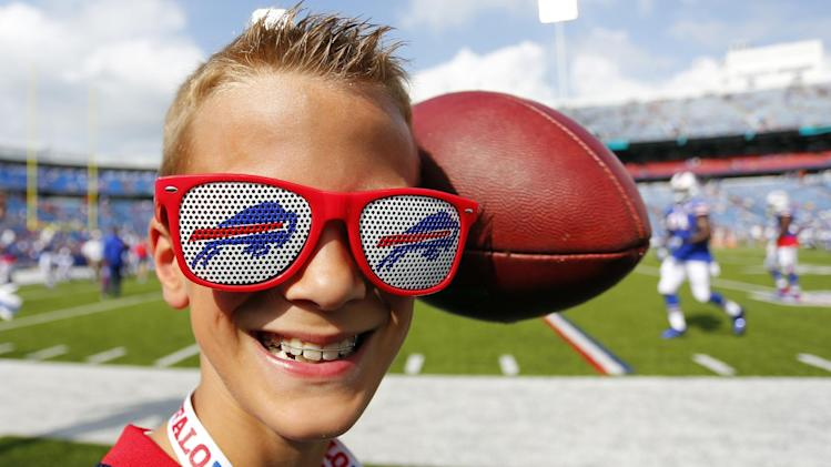 Buffalo Bills fan Jackson Jones, 10, of Grand Island, N.Y. smiles as a ball narrowly misses him while the Tampa Bay Buccaneers and the Bills warm up before a preseason NFL football game Saturday, Aug. 23, 2014, in Orchard Park, N.Y