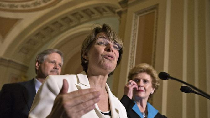Sen. Amy Klobuchar, D-Minn., center, joins Sen. Debbie Stabenow, D-Mich., chairwoman of the Senate Agriculture Committee, right, and Sen. John Hoeven, R-ND, left, to speak to reporters as the Senate votes on a farm bill that sets policy for farm subsidies, food stamps and other farm and food aid programs for the next five years, at the Capitol in Washington, Monday, June 10, 2013.  (AP Photo/J. Scott Applewhite)