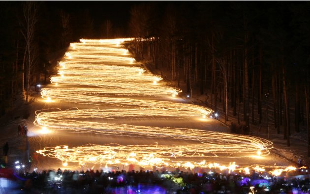 Spectators watch skiers descending down from the slope while holding lit torches in the town of Zheleznogorsk