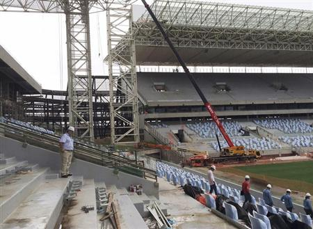 An official (L) from Brazil's World Cup organizers accompanies visitors on a tour inside the Arena Pantanal soccer stadium, which will host several matches of the 2014 World Cup in Cuiaba, Februar