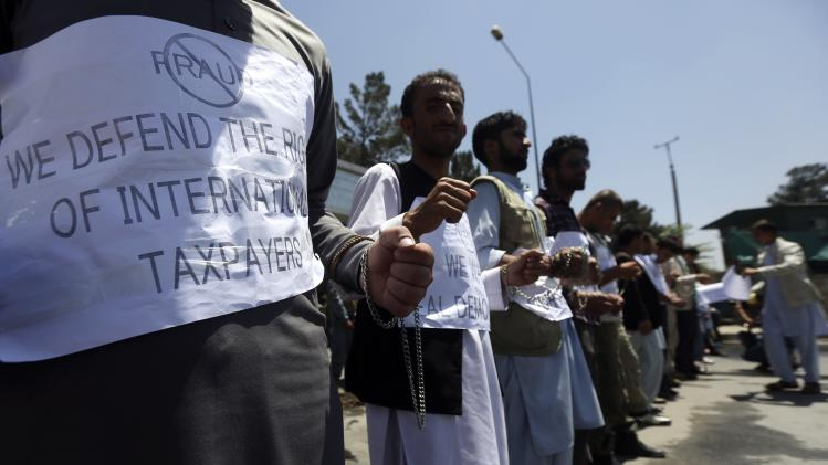 Supporters of Afghan presidential candidate Abdullah Abdullah stand, chained together, during a protest in Kabul