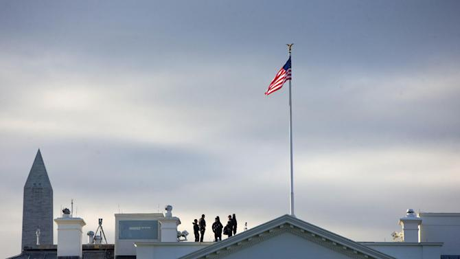 ** UPDATES THE CHARGES FILED AGAINST DOMINIC ADESANYA ** Members of the Secret Service Counter Assault team are seen on the rooftop of the White House in Washington, Thursday, Oct. 23, 2014. Dominic Adesanya, the 23-year-old Maryland man who climbed over the White House fence was ordered held without bond in an appearance Thursday before a federal magistrate judge. He has been charged with unlawfully entering the restricted grounds of the White House and harming two police dogs. (AP Photo/Pablo Martinez Monsivais)