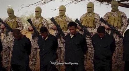 Islamic State militants stand behind what are said to be Ethiopian Christians in Wilayat Fazzan, in this still image from an undated video made available on a social media website