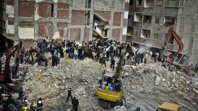 Egyptians stand in rubble after an eight story building collapsed in Alexandria, Egypt, Wednesday, Jan. 16, 2013. Egypt's official MENA news agency says at least fourteen people have been killed. It was not immediately known what caused the building to collapse, but violations of building specifications have been blamed in the past for similar accidents. (AP Photo)