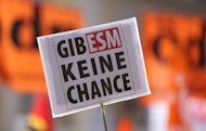 "A demonstrator waves a banner reading ""Don't give ESM a chance"" on September 08 during a demonstration against the European Stability Mechanism (ESM) in Karlsruhe, southern Germany. The eurozone cleared a key hurdle towards resolving its debt crisis Wednesday as Germany's top court approved a new European firewall for ratification, with some minor conditions"