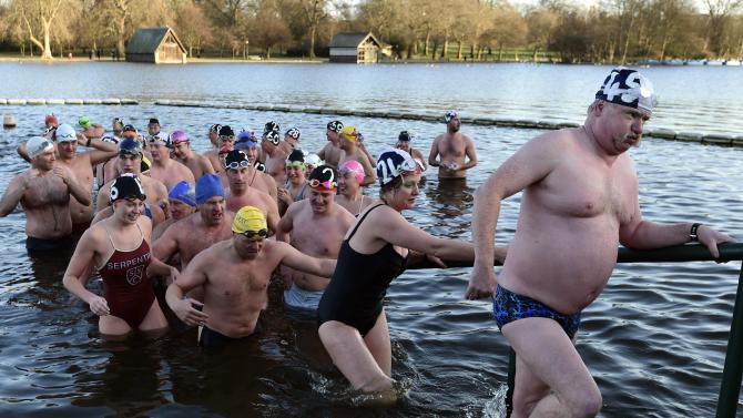 Competitors climb out of the water after taking part in the Peter Pan Cup open water swim in the Serpentine Lake at Hyde Park in London