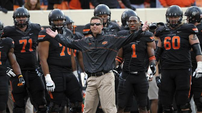 "In this Oct. 27, 2012, file photo, Oklahoma State coach Mike Gundy, center, questions an official's call denying Oklahoma State a touchdown during the second half of an NCAA college football game against TCU in Stillwater, Okla. An NCAA committee passed a proposal Wednesday, Feb. 12, 2014, that would allow defenses time to substitute between plays by prohibiting offenses from snapping the ball until 29 seconds are left on the 40-second play clock. ""The 10-second rule is like asking basketball to take away the shot clock - Boring!"" Gundy tweeted Thursday. ""It's like asking a blitzing linebacker to raise his hand."""