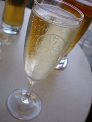 A glass of sparkling wine is served on a table.
