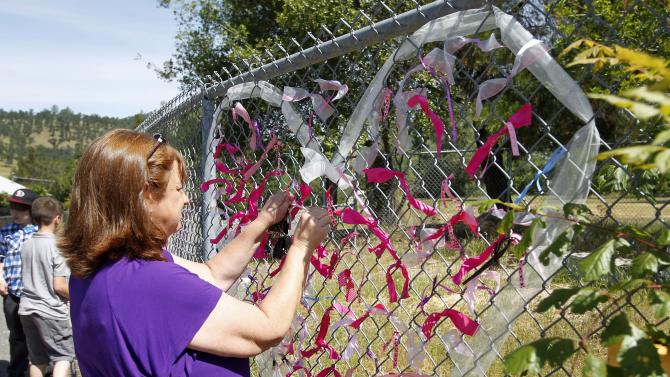 Teacher Cecilia Richardson ties a ribbon honoring murder victim honoring murder victim, Leila Fowler, at Jenny Lind Elementary School in Valley Springs, Calif., Monday April 29, 2013. Authorities are searching for the killer of  Fowler, 8, who was found murdered by her 12-year-old brother in the family's Valley Springs home Saturday. (AP Photo/Rich Pedroncelli)