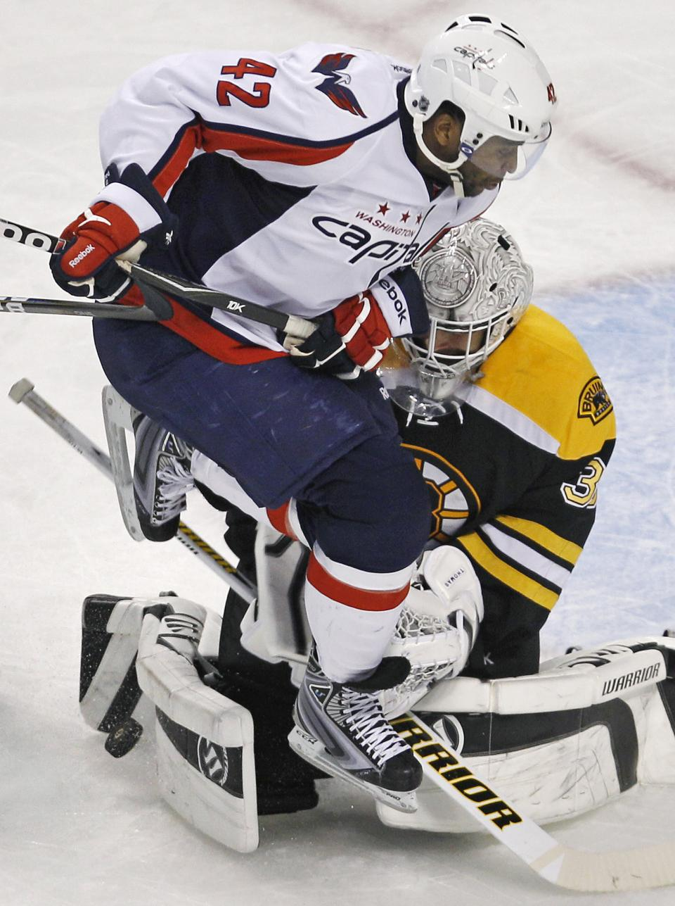 Washington Capitals right wing Joel Ward (42) leaps over the stick of Boston Bruins goalie Tim Thomas (30), who makes the save, during the second period of Game 7 of an NHL hockey Stanley Cup first-round playoff series, in Boston on Wednesday, April 25, 2012. (AP Photo/Charles Krupa)
