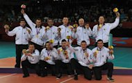 Bosnia's team pose on the podium with their gold medals after beating Iran in the final of the sitting volleyball competition during the London 2012 Paralympic Gamesat at the Excel Arena in east London