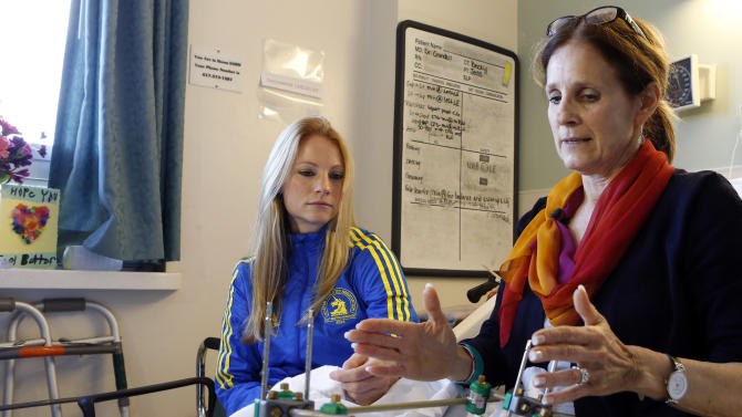 Beth Roche, right, whose left leg was severely injured by one of the bombs that exploded near the Boston Marathon finish line, sits on her bed with her daughter Rebecca Roche, left, at Spaulding Rehabilitation Hospital in Boston, Wednesday, April 24, 2013.  Beth Roche, who ran the Chicago Marathon last fall, was in Boston to watch her Rebecca run the Boston Marathon. (AP Photo/Bizuayehu Tesfaye)