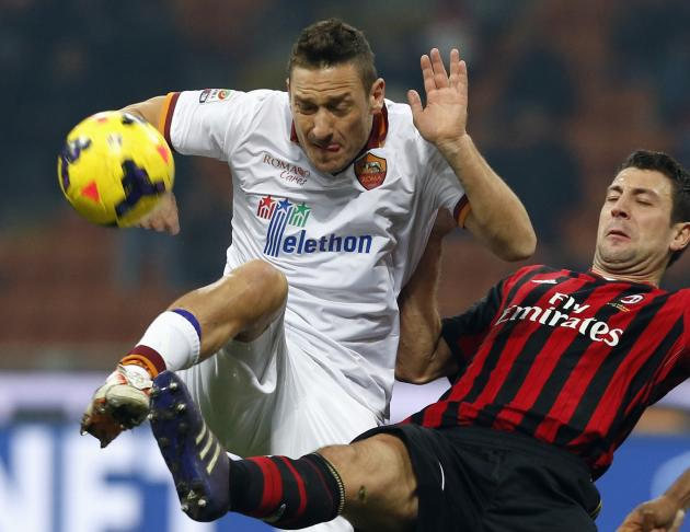 AC Milan's Daniele Bonera challenges AS Roma's Francesco Totti during their Italian Serie A soccer match at San Siro stadium in Milan