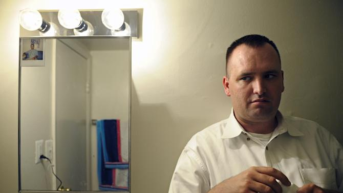 """In this Aug. 23, 2012 photo, Kevin Earley, 33, holds a bottle of his antipsychotic medication as he stands next to the medicine cabinet which has an old photo taped to it, in the bathroom of his Vienna, Va., apartment that he shares with a roommate. Of the photo, Earley says, """"It reminds me to take my medicine every day and reminds me of where I have been and what I have been through."""" (AP Photo/Cliff Owen)"""