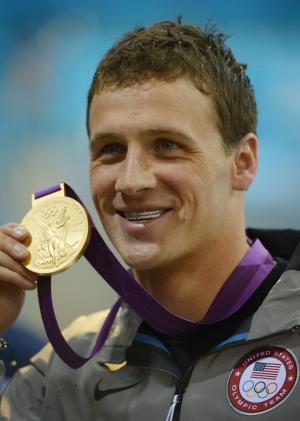 United States' Ryan Lochte poses with his gold medal for the men's 400-meter individual medley swimming final at the Aquatics Centre in the Olympic Park during the 2012 Summer Olympics in London, Saturday, July 28, 2012. (AP Photo/Mark J. Terrill)