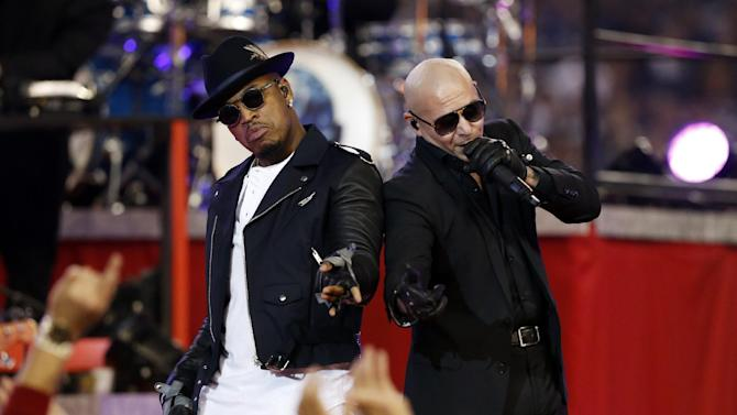 Rappers Ne-Yo, left, and Pitbull perform at half time at an NFL football game between the Philadelphia Eagles and the Dallas Cowboys, Thursday, Nov. 27, 2014, in Arlington, Texas. (AP Photo/John F. Rhodes)