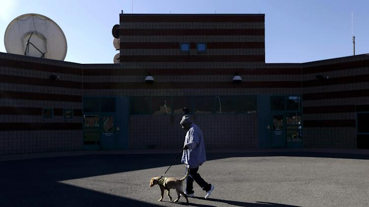 In this Nov. 26, 2012 photo, inmate Hazard Wilson walks Yardley, a veteran assistance dog in training, on the grounds of Western Correctional Institution in Cresaptown, Md. Yardley is one of three dogs assigned since September to inmates at the maximum-security prison for basic training as service dogs for disabled military veterans. The inmates, who are also veterans, are among the state's first prisoners to join a national trend of training service dogs in correctional institutions. Professional trainers say prison-raised dogs tend to graduate sooner and at higher rates than those raised traditionally in foster homes because puppies respond well to the consistency and rigid schedules of prison life. (AP Photo/Patrick Semansky)