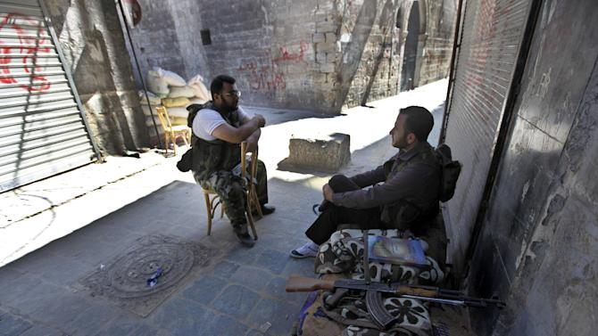In this picture taken on Monday September 24, 2012, Free Syrian Army fighter sit at one of their positions next to closed shops at the souk in the old city of Aleppo city, Syria. Fires sparked by clashes between government troops and rebels raged through the medieval marketplace of Aleppo on Saturday, destroying hundreds of shops lining the vaulted passageways where foods, fabrics, perfumes and spices have been sold for centuries, activists said. (AP Photo/Hussein Malla)