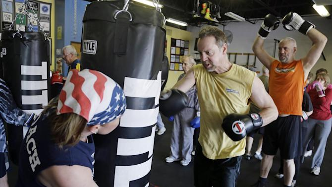In this March 19, 2013 photo, Kristy Rose Follmar, left,  holds the heavy bag for Tom Timberlake during a workout at Rock Steady Boxing in Indianapolis. Follmar, began her boxing career as an Indiana Golden Gloves Women's Champion and later a  world-ranked professional boxer, leads the class at Rock Steady Boxing teaching physical exercise to people who are living with Parkinson's. (AP Photo/Michael Conroy)