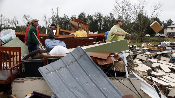 """File - In this April 11, 2013 file photo, Shuqualak, Miss. residents begin cleanup of debris from homes after a tornado plowed through rural sections of eastern Mississippi, killing at least one person and causing widespread damage and power outages, officials said. The Storm Prediction Center plans to broaden its days-in-advance warning system for severe weather after finding the days labeled with a """"Slight Risk"""" tag turned out to have storms that were fairly stout _ and even deadly. (AP Photo/Rogelio V. Solis, File)"""