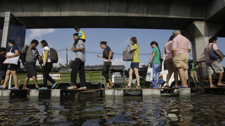 In this Thursday, Nov. 10, 2011 file photo, pedestrians use an elevated makeshift walkway to avoid the floodwaters in Bangkok, Thailand. The year 2011 brought a record heat wave to Texas, massive floods in Bangkok and an unusually warm November in England. How much has global warming boosted the chances of events like that? Quite a lot in Texas and England, but apparently not at all in Bangkok, according to new analyses released Tuesday, July 10, 2012. It found no sign that climate change played a role in that event, noting that the amount of rainfall was not very unusual. The scale of the flooding was influenced more by factors like reservoir operation policies, researchers wrote. (AP Photo/Aaron Favila)