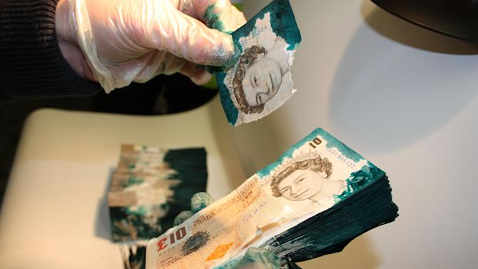 This undated photo provided by security company G4S shows bills treated with glue and dye as part of its new security system. British authorities said Wednesday, May 23, 2012, that three bandits were foiled when their attempt to pry open a stolen cash box ran up against the new security system that slathered the bills with glue. The bandits were part of a gang that ambushed a cash delivery man working for security company G4S in south London on Jan. 16, 2011. The group stole his cash box but ran into trouble when they retreated to a parking lot to try to open it. (AP Photo/Courtesy G4S)